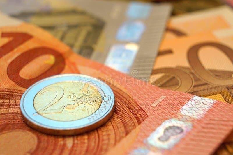 Euroräkningar och en myntmakro arkivfoto