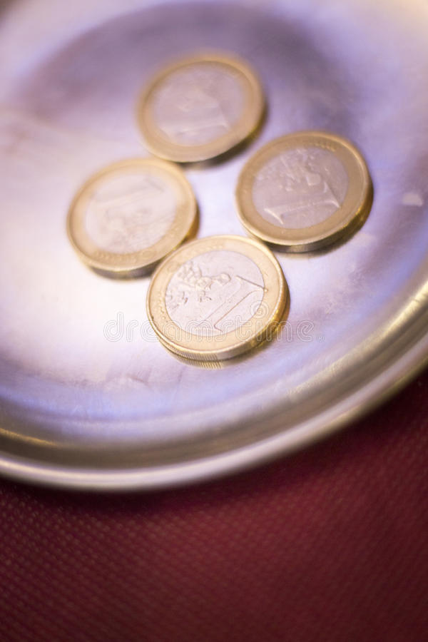 Euros coins change money. In restaurant on metal tray paying meal check stock photography