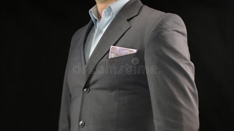 Euros en bolsillo del traje del hombre de negocios, el ahorro del dinero, la renta y el inicio acertado foto de archivo