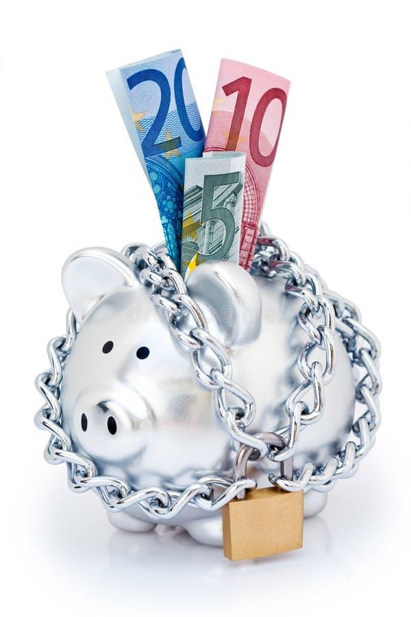 Euros in padlocked piggy bank stock photography