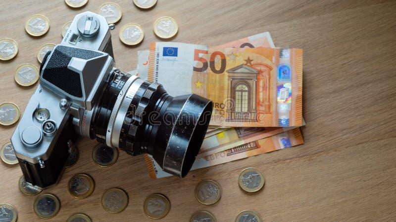 Eurosedlar, mynt och en kamera på en ljus träbakgrund royaltyfri bild