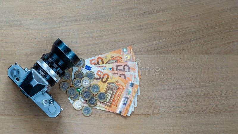 Eurosedlar, mynt och en kamera på en ljus träbakgrund royaltyfria bilder