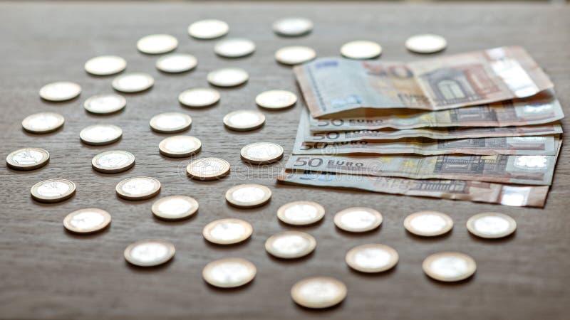 50 eurosedlar och 1 euro mynt på en ljus wood bakgrund royaltyfri bild