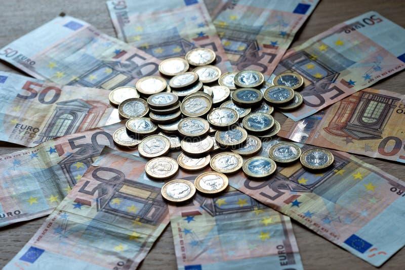 50 eurosedlar och 1 euro mynt på en ljus wood bakgrund arkivfoton