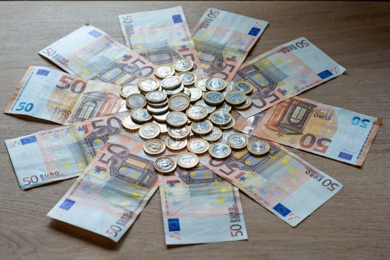 50 eurosedlar och 1 euro mynt på en ljus wood bakgrund fotografering för bildbyråer