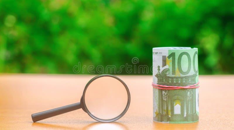 Eurosedlar och förstoringsglas Begreppet av att finna k?llor av investeringen och sponsorer Finna pengar Medm?nskliga fonder royaltyfria foton