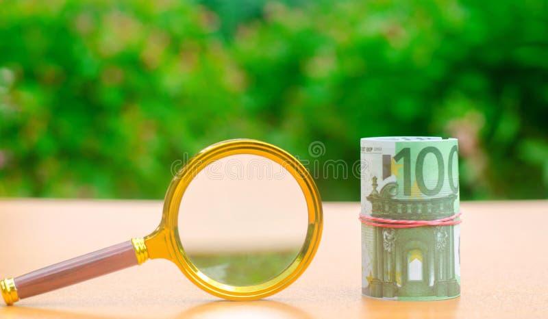 Eurosedlar och förstoringsglas Begreppet av att finna k?llor av investeringen och sponsorer Finna pengar Medm?nskliga fonder royaltyfri fotografi