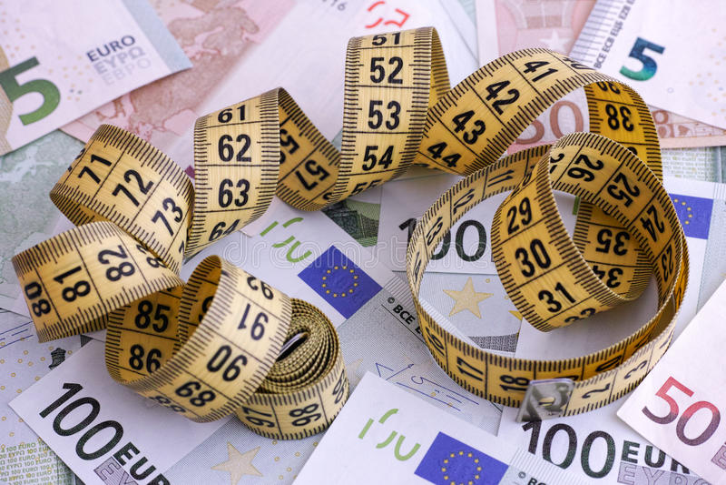Eurosedlar och gul måttband royaltyfri bild