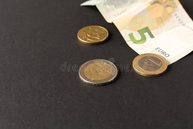 5 eurosedlar och mynt p? m?rk bakgrund close upp Begreppet av besparingar arkivfoton