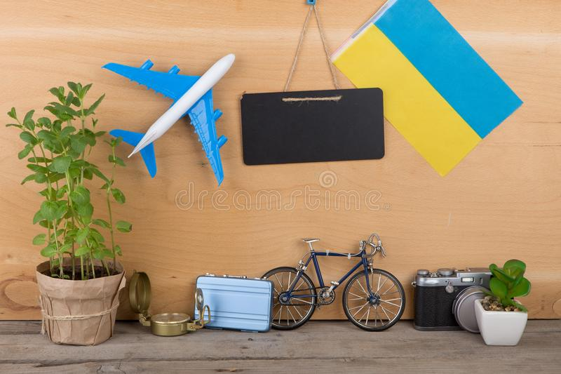 Eurovision 2017 concept - blank blackboard, flag of the Ukraine, airplane model, little bicycle and suitcase, camera, compass. On wooden background stock image