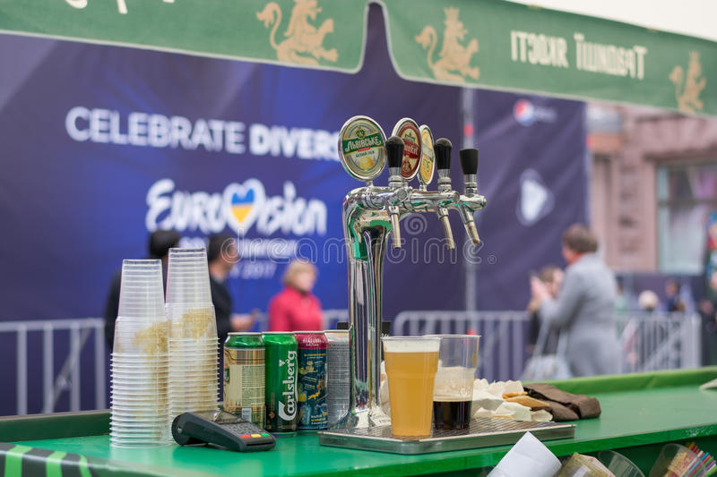 Eurovision Village. Ukraine, Kyiv. 05.12.2017. Editorial. Bar st. And with beer in front of board with logo Eurovision in the Eurovision fan zone on the royalty free stock images