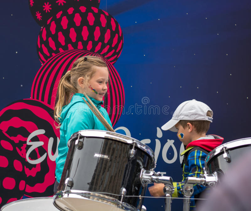 Eurovision Village. Ukraine, Kyiv. 05.12.2017. Editorial. Children with face-art playing drums in front of Board with logo royalty free stock photos