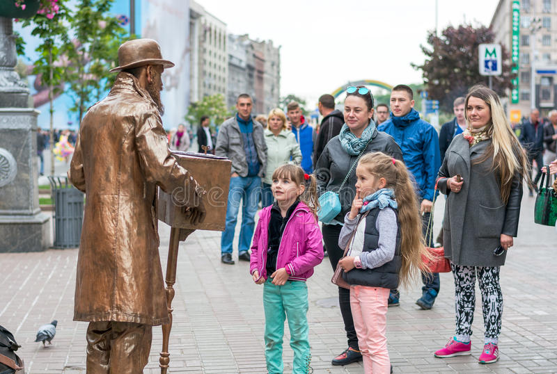 Eurovision Village. Ukraine, Kyiv. 05.12.2017. Editorial. Children are looking at a living sculpture in the Eurovision fan zone o. N the Khreshchatyk Street in stock photography