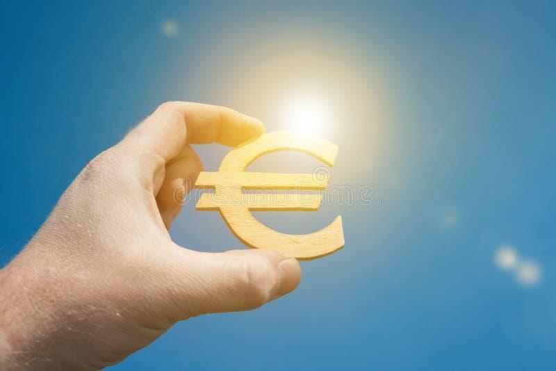 Eurowährungszeichen in der Hand eines Geschäftsmannes, gegen den Himmel und die Sonne lizenzfreie stockbilder