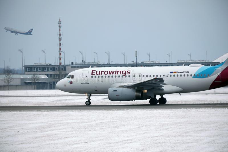 Eurowings Airbus A319-100 D-AGWB landing in Munich Airport. Eurowings Airbus A319-100 D-AGWB landed in Munich Airport, winter time with snow on runway stock images