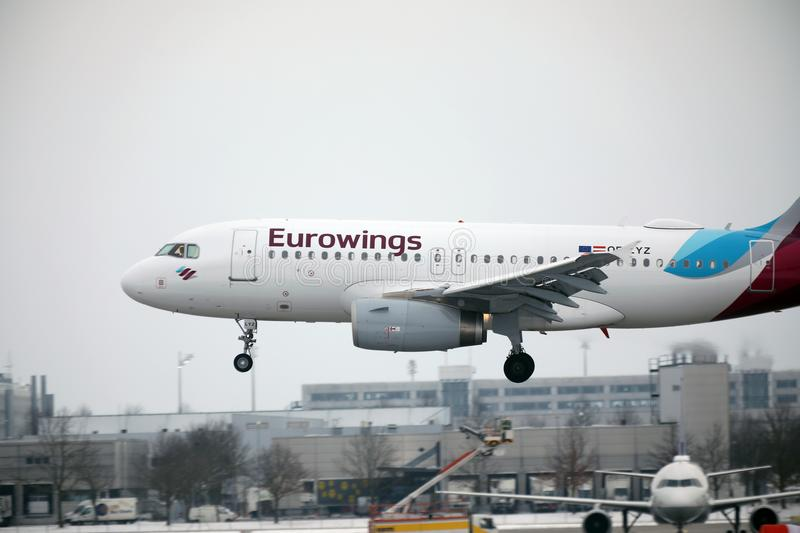 Eurowings Europe Airbus A319-100 OE-LYZ landing in Munich Airport. Winter time with snow on runway royalty free stock images