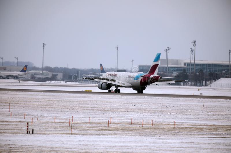 Eurowings Europe Airbus A319-100 OE-LYZ landing in Munich Airport. Winter time with snow on runway royalty free stock image