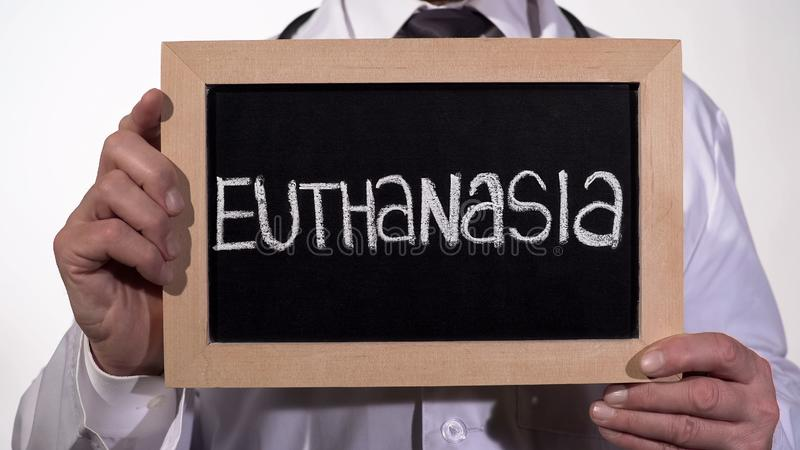 Euthanasie geschrieben auf Tafel in Doktorhände, umstrittenes Sozialproblem lizenzfreie stockfotografie