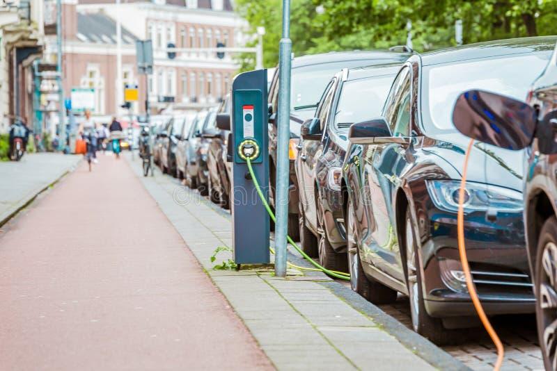 EV auto of Elektrische auto bij het laden post met de gestopte levering van de machtskabel royalty-vrije stock foto's