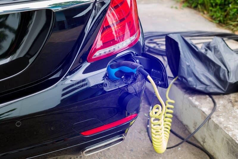 EV-Auto oder -Elektroauto an Ladestation mit der Stromkabelversorgung angeschlossen, aufladendes hybrides Auto, umweltfreundliche stockbilder