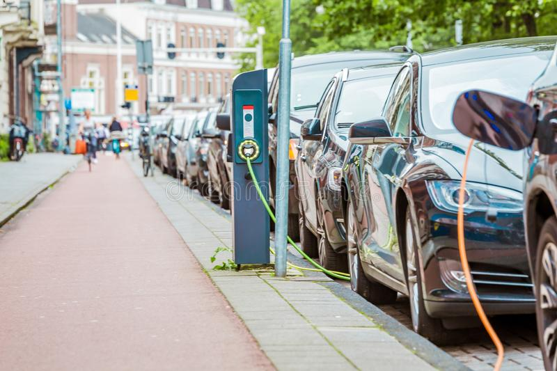 EV Car or Electric car at charging station with the power cable supply plugged. In Amsterdam, Holland royalty free stock photos