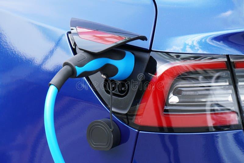 EV of Elektrische auto bij het laden post met insteekvoedingkabel stock afbeeldingen