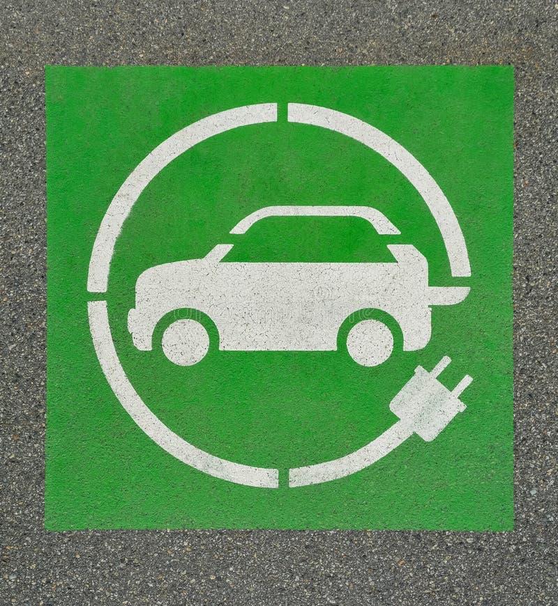 EV - segno della stazione di carico del veicolo elettrico su asfalto Segno del ` del ` E sul fondo dell'asfalto immagini stock