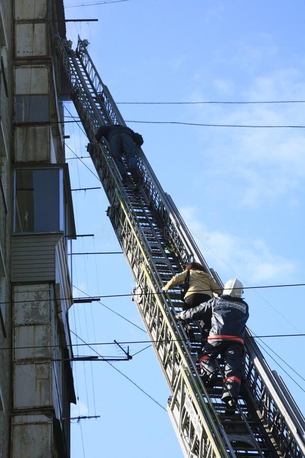 Evacuación de quemado abajo de personas por la escalera de incendios fotos de archivo libres de regalías