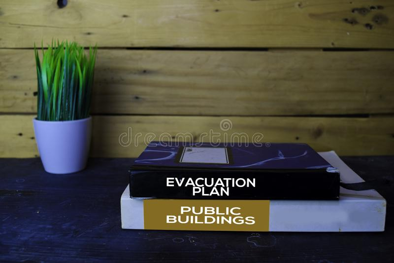 Evacuation Plan and Public Buildings write on books with wooden table background royalty free stock image