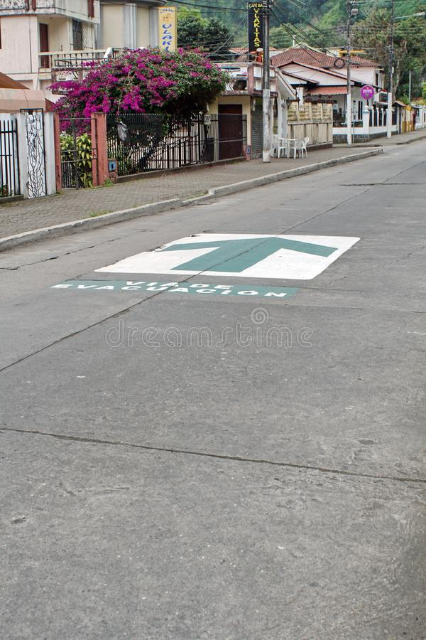 Evacuation route sign in Banos, Ecuador. Evacuation route arrows painted on the road in Banos, Ecuador royalty free stock images