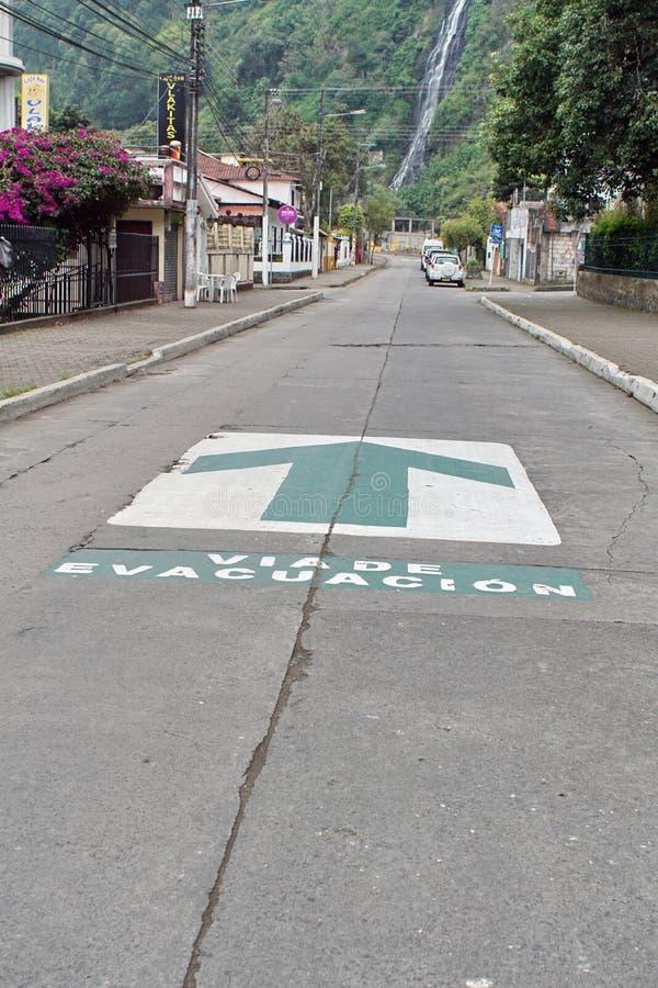 Evacuation route sign in Banos, Ecuador. Evacuation route arrows painted on the road in Banos, Ecuador royalty free stock image