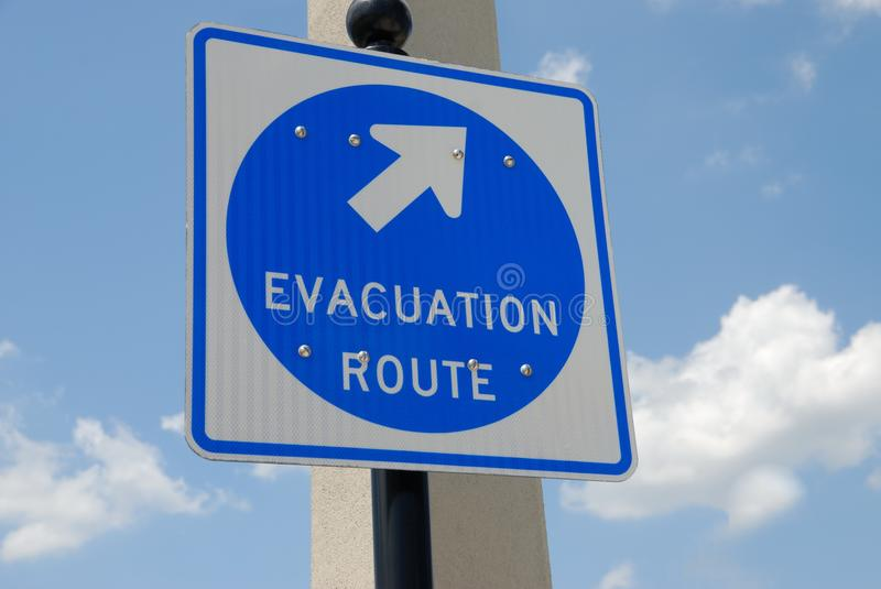 Evacuation route sigh. Directional American evacuation route sign with blue sky and cloudscape background stock image