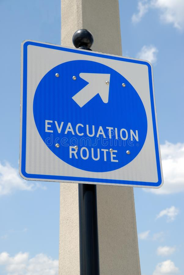 Evacuation route sign. With blue sky and cloudscape background royalty free stock photo