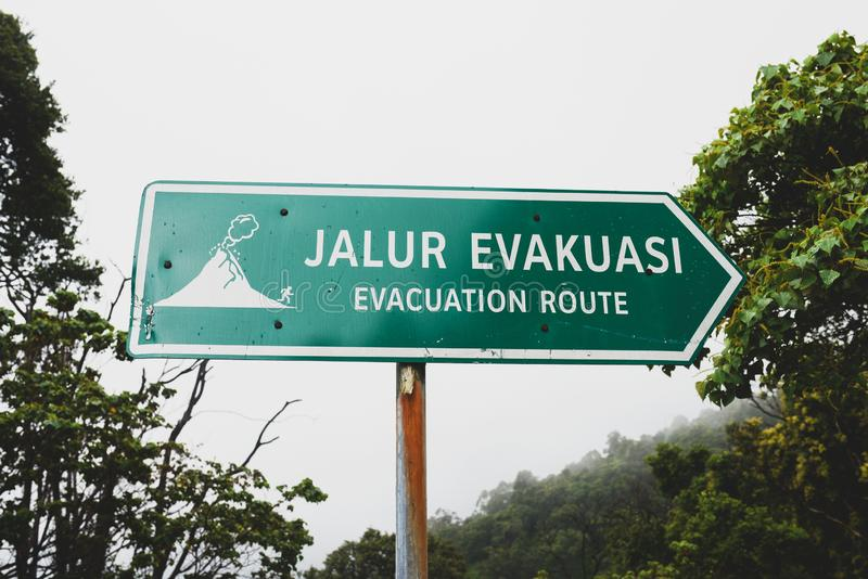 Evacuation route sign. Evacuation sign volcano on the road stock images