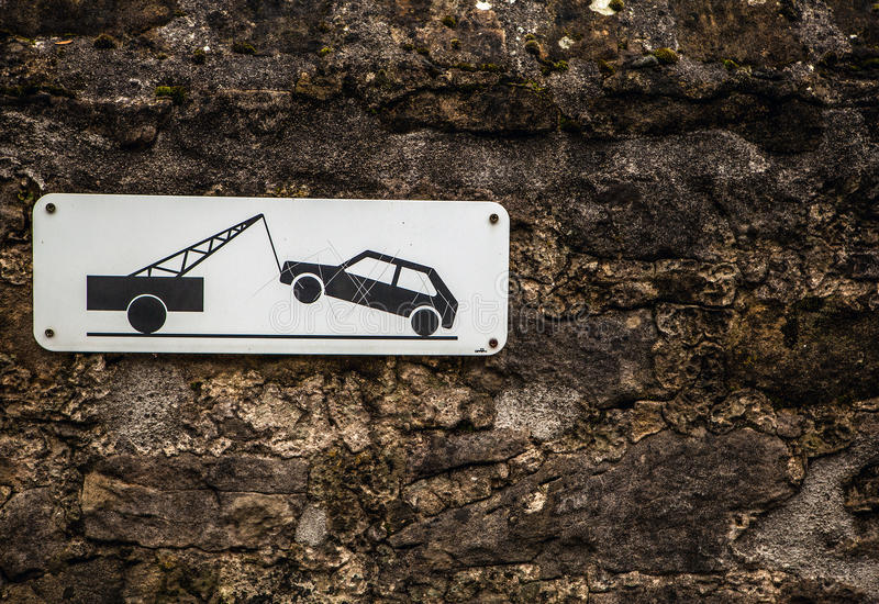 Evacuation on tow truck sign on old stone wall.  stock image