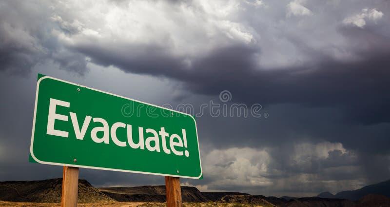 Evakuera det gröna vägmärket och stormiga moln royaltyfri foto