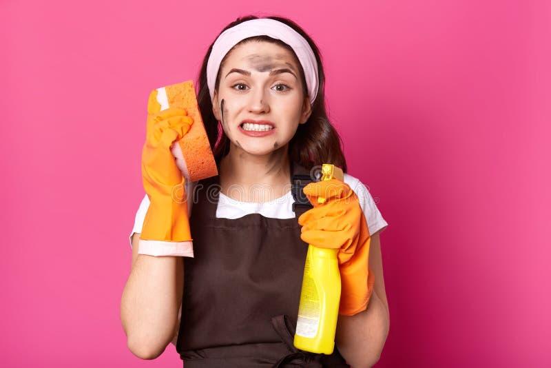 Evakuerat emotionellt rengöringsmedelanseende som isoleras över rosa bakgrund i studio och att rymma tvättlapp nära örat och tvät arkivfoto