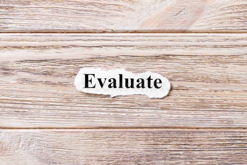 Evalúe de la palabra en el papel Concepto Palabras Evaluate en un fondo de madera imagen de archivo