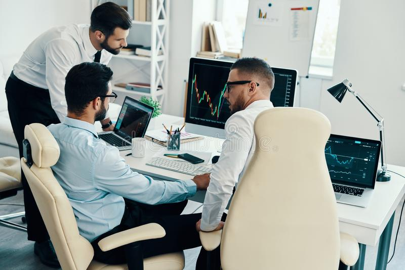 Evaluating risks. Group of young modern men in formalwear analyzing stock market data while working in the office royalty free stock images
