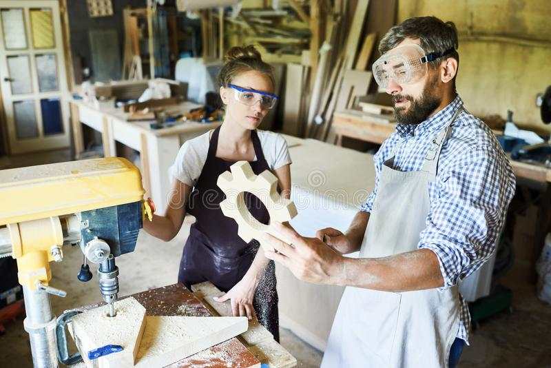 Evaluating Work Results. Group of hard-working carpenters looking at just finished wooden detail with concentration while standing at drill press machine, their royalty free stock photo