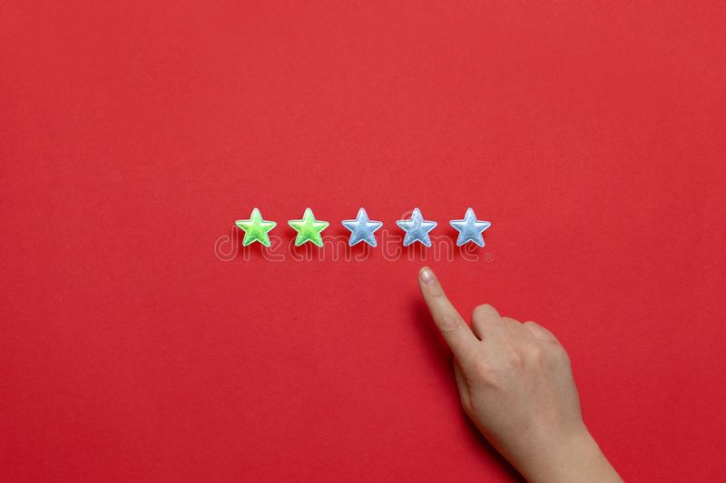 Evaluation of the quality of service and the provision of services. Female hand leaves a rating of two stars out of five possible royalty free stock photos