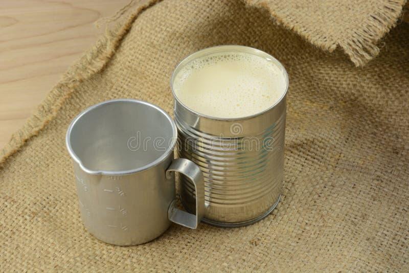 Evaporated mjölkar och den retro mäta koppen royaltyfria foton