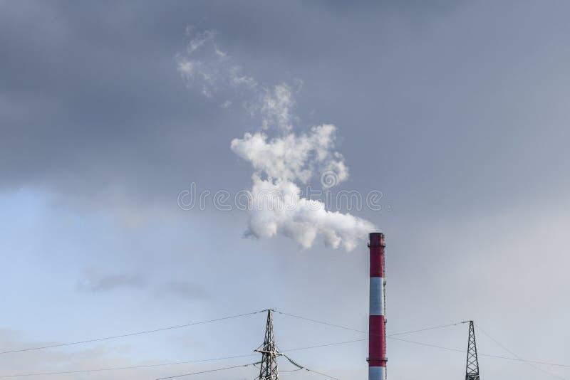 Evaporazione nociva da un tubo Camino della fabbrica con fumo bianco ed il cielo contaminato fotografia stock