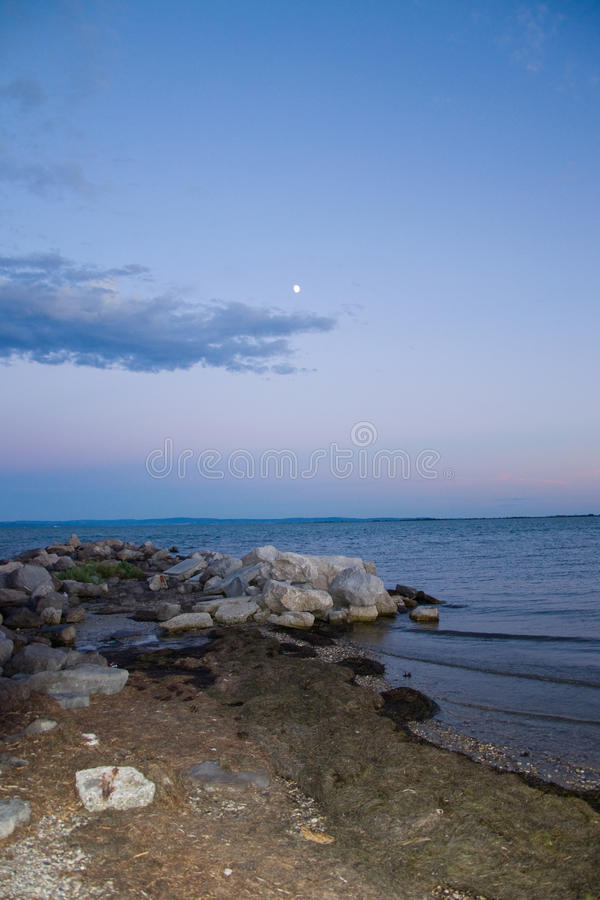 Evening beach. Pebble beach with drifted seaweed, incoming tide and light passing clouds over the blue sky with the moon ; *RAW format available at request stock image