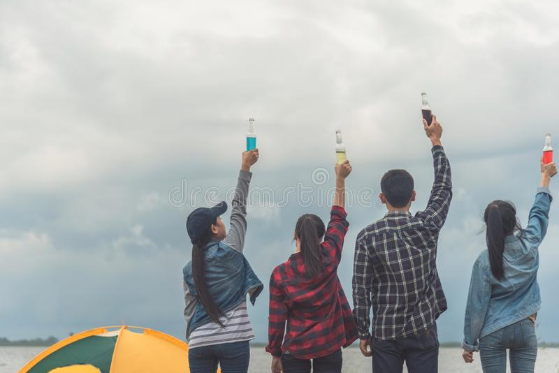 Evening at the beach. Group of friends are drinking beers and having fun, sitting in the sand around a campfire. They are smiling. Doing toast and clinking royalty free stock images