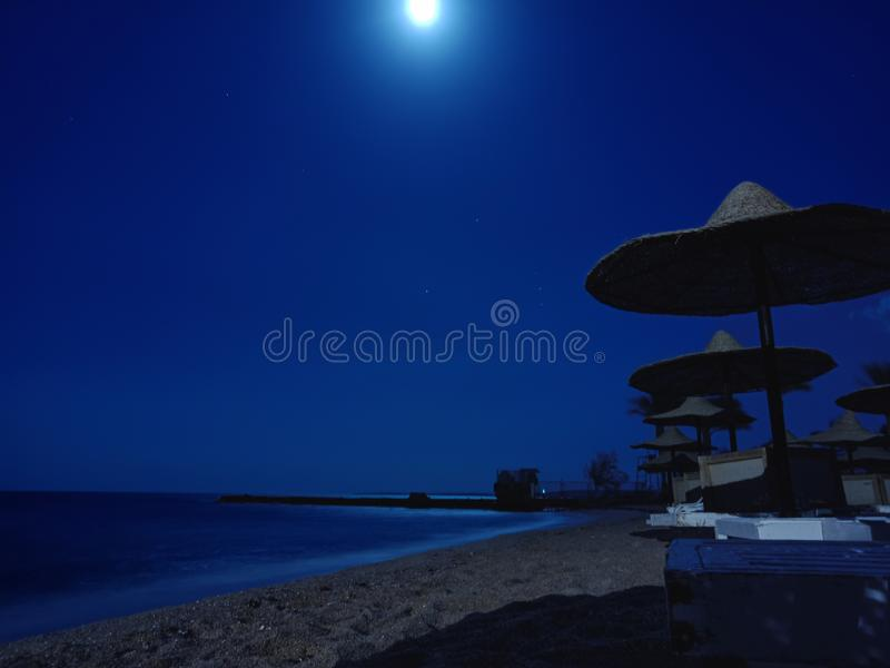Evening on the beach with straw umbrellas. Hurghada, Egypt royalty free stock photography