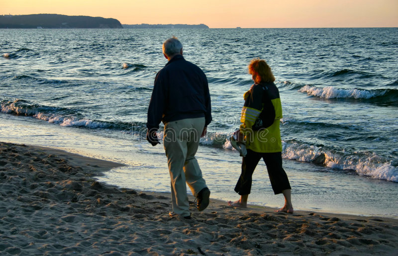 Evening beach stroll stock images