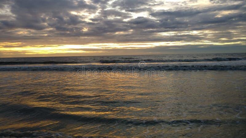 Evening beach sunset with rainy weather royalty free stock photo