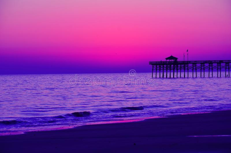 Evening beachfront view. Violet colors mesmerize and relax at sundown watching fishermen on the pier in the distance stock photography