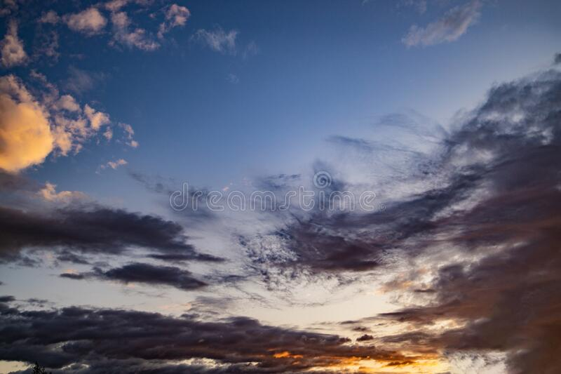 Evening blue sky with dark clouds lit by the orange sun stock photo